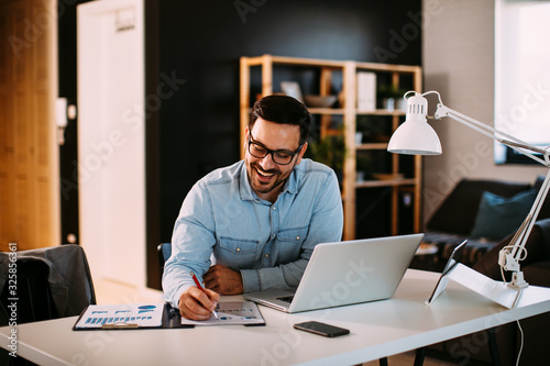 Fotografie, Obraz Young business man working at home with laptop and papers on desk