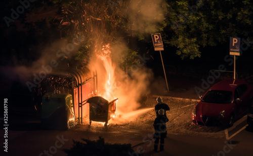 Photo Firefighters Extinguish Burning Plastic Dumpster near Parking Lot at Night