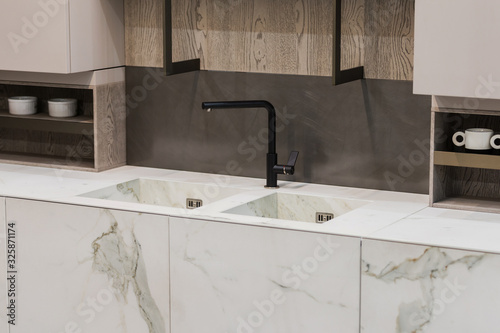 Valokuva Modern kitchen white marble texture, black faucet and marble sink, hanging woode