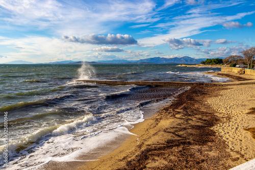 Scenic agitated Aegean Sea coastline view with breakwater and empty November off Wallpaper Mural