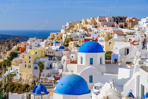 Fototapeta Blue domed church and traditional white houses facing Aegean Sea in Oia, Santorini, Greece obraz