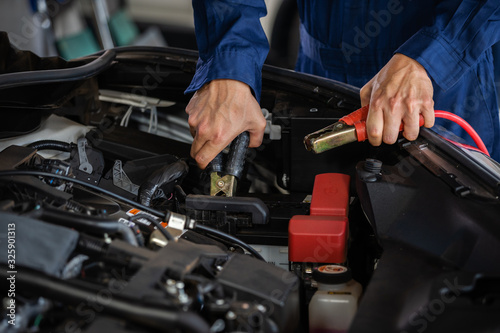 Fotomural mechanic hand charging battery car with electricity through jumper cables