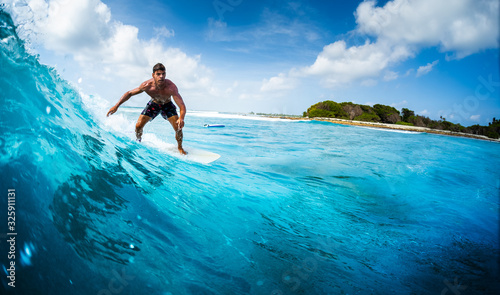 Fotografía Young athletic surfer rides the ocean wave on Sultans surf spot in Maldives