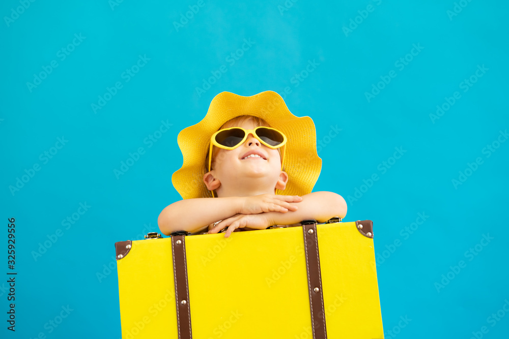 Fototapeta Portrait of happy child with yellow suitcase. Summer vacation concept