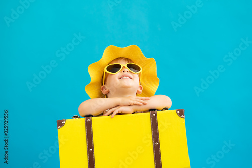 Portrait of happy child with yellow suitcase Fotobehang