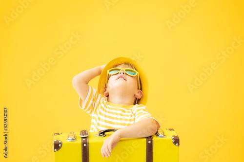 Obraz Portrait of happy child with retro yellow suitcase - fototapety do salonu