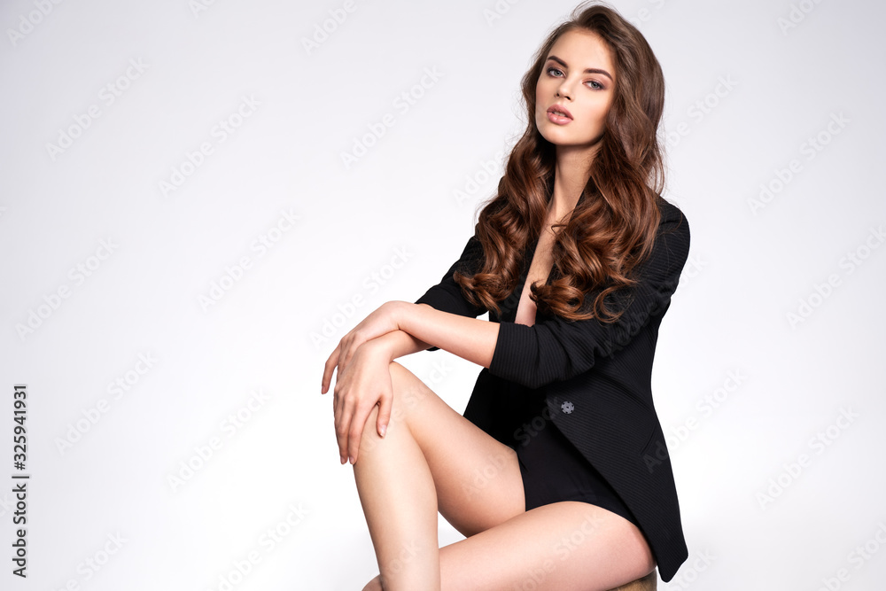 Fototapeta Portrait of a beautiful woman with a long hair in a black clothes. Young brunette woman in black sits on chair. Beautiful fashion model with brown hair, isolated on white background.