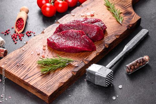 Fototapeta Fresh Raw Beef steak Mignon, with salt, peppercorns, thyme, tomatoes obraz