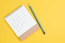 White Clean Calendar On Solid Yellow Background With Pencil And Copy Space, Business Meeting Planning, Travel Schedule Or Project Milestone And Reminder Concept