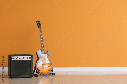 Foto Modern guitar and amplifier near color wall
