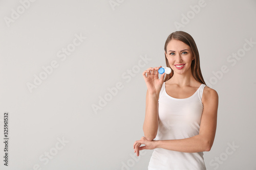 Woman with contact lenses on light background Wallpaper Mural