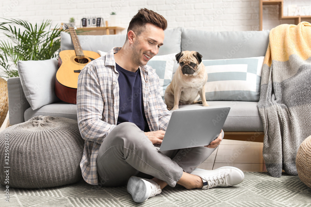 Fototapeta Handsome man with laptop and cute pug dog at home