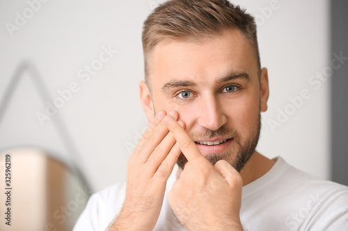 Young man putting in contact lenses at home Canvas Print