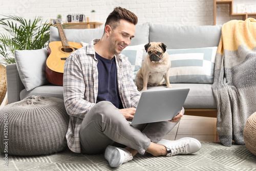 Fototapeta Handsome man with laptop and cute pug dog at home obraz