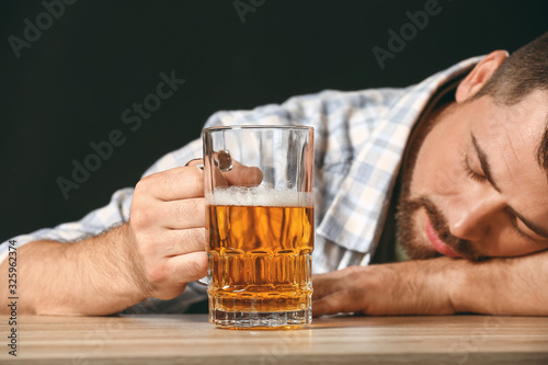 Fotografía Drunk man with beer at table. Concept of alcoholism