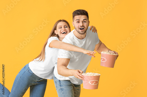 Fototapeta Emotional young couple with popcorn on color background