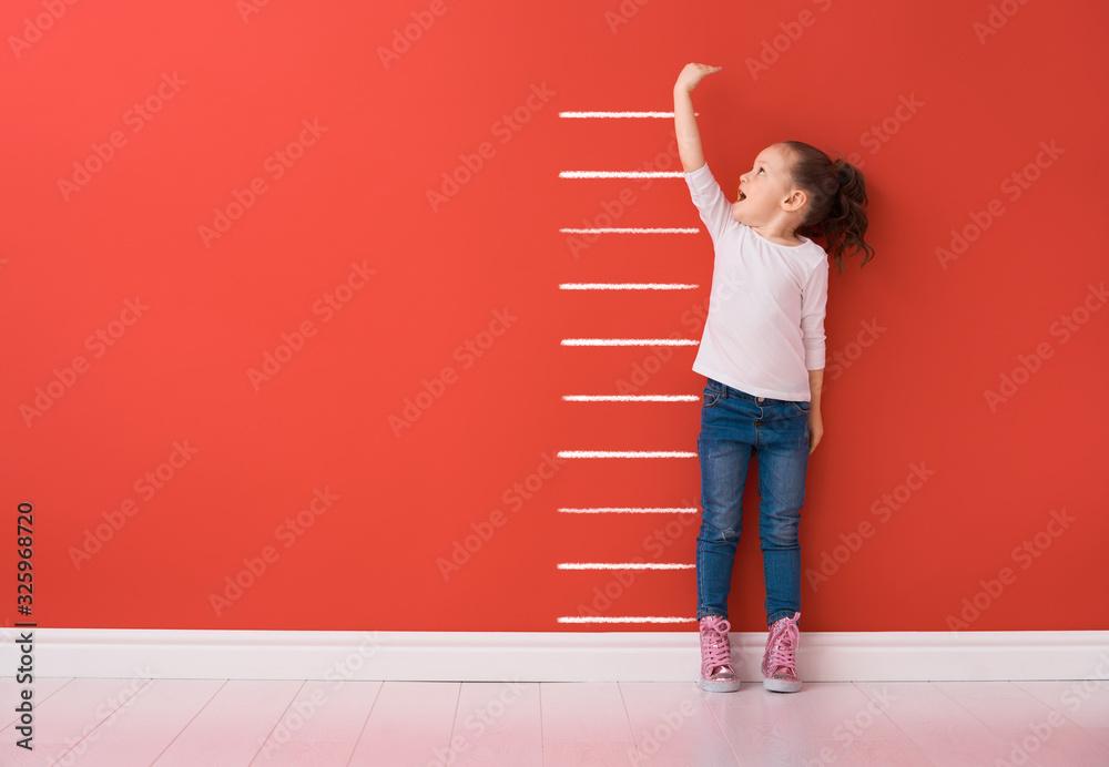 Fototapeta Kid is measuring the growth