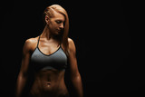 Portrait of a fit young woman posing wearing a sports bra against black background. Determined athlete in the studio. Copy space, black background, sports banner.