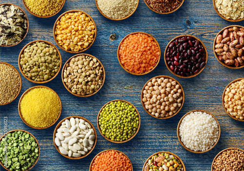 Cereals and legumes in wooden bowls on old wooden background Canvas Print