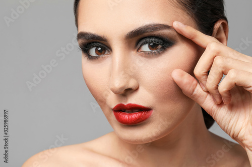 Fototapety, obrazy: Young woman with beautiful makeup on grey background