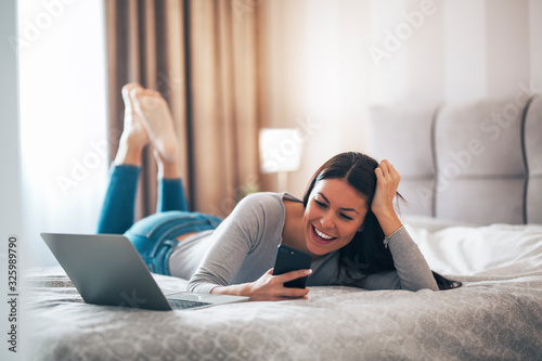Fototapeta Beautiful girl laughing while using phone on the bed. obraz