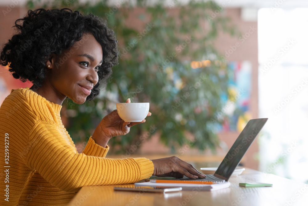 Fototapeta Female blogger drinking coffee and working with laptop at cafe