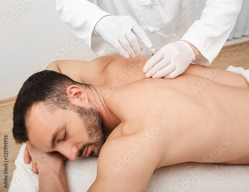 Acupuncturist inserting a needle into a male back Canvas Print