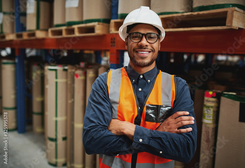 Obraz Portrait smiling worker wearing orange vest and white helmet with arms crossed in a large warehouse smiling - fototapety do salonu