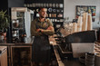 Leinwandbild Motiv Thoughtful afro-american small coffee shop owner standing behind counter wearing apron with crossed arms looking away