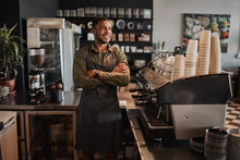 Thoughtful Afro-american Small Coffee Shop Owner Standing Behind Counter Wearing Apron With Crossed Arms Looking Away