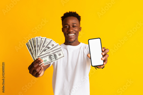 Fototapeta Excited african man holding lots of money in dollar currency obraz
