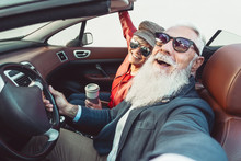 Happy Senior Couple Taking Selfie On New Convertible Car - Mature People Having Fun Together During Road Trip Vacation - Elderly Lifestyle And Travel Transportation Concept