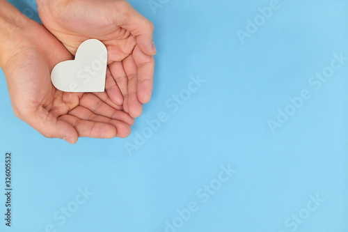 Fotografering Hands holding a white heart in blue background