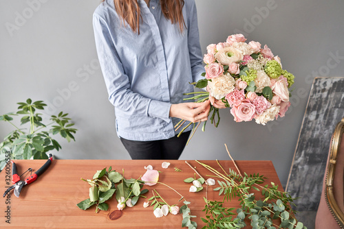 Woman florist creating beautiful bouquet in flower shop. Work in flower shop. Flowers delivery.