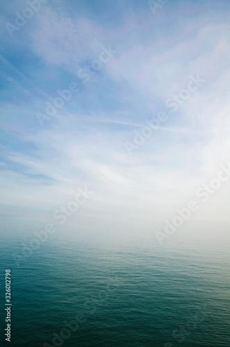Fototapeta Scenic view of sky and sea blending into a misty white horizon obraz