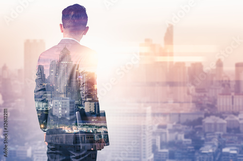The double exposure image of the business man using a smartphone during sunrise overlay with cityscape image Canvas Print