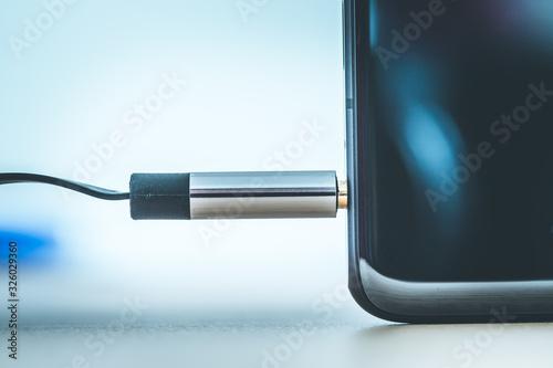 Audio jack concept: Connecting audio jack to a black mobile phone, close up Canvas Print