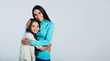 canvas print picture - Mom's hugs. Close-up photo of an attractive woman with a warm smile hugging her little daughter with long beautiful hair, both are looking in the camera.