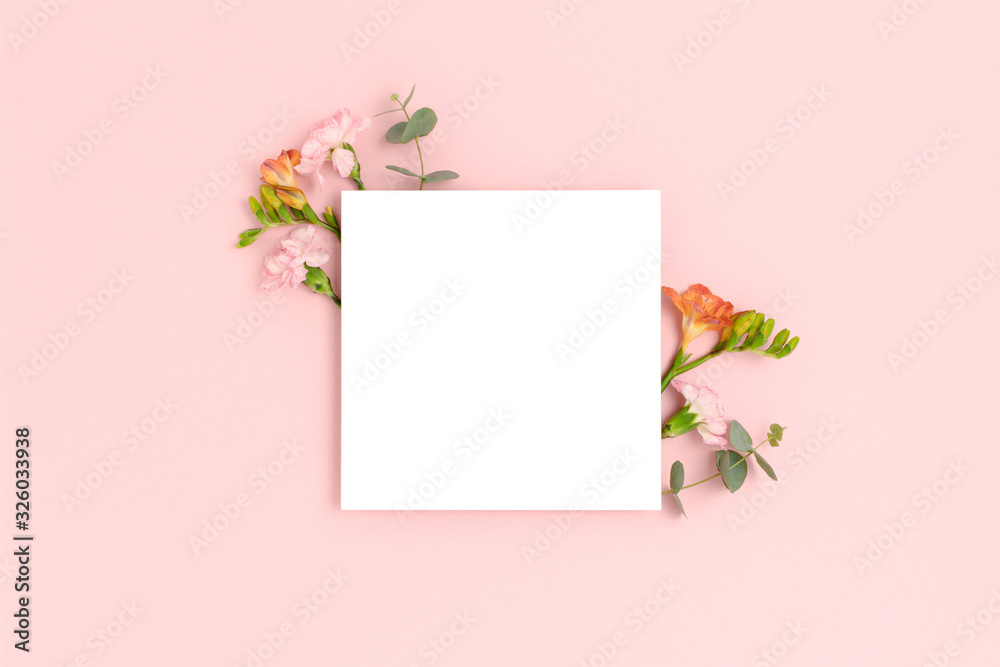 Fototapeta Blank paper card mockup with frame made of flowers and eucalyptus. Festive floral composition with copy space on a pink pastel background.