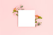canvas print picture - Blank paper card mockup with frame made of flowers and eucalyptus. Festive floral composition with copy space on a pink pastel background.