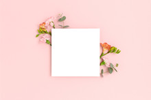 Blank Paper Card Mockup With Frame Made Of Flowers And Eucalyptus. Festive Floral Composition With Copy Space On A Pink Pastel Background.