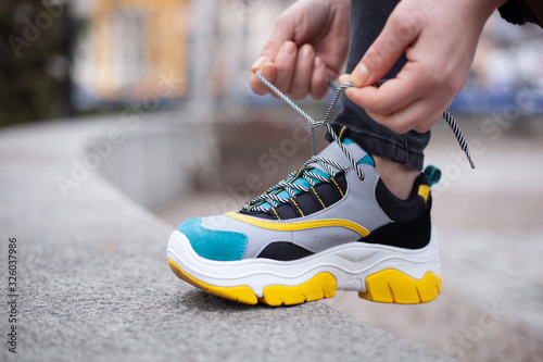 Fotografia Girl tying shoelaces on multi-colored sneakers of yellow, white, black and blue