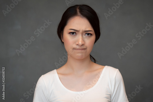 face portrait of sad unhappy girl; portrait of upset angry frustrated Chinese or Fototapeta