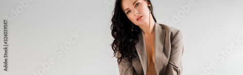 Fototapeta panoramic shot of sexy and stylish woman in suit looking at camera isolated on g
