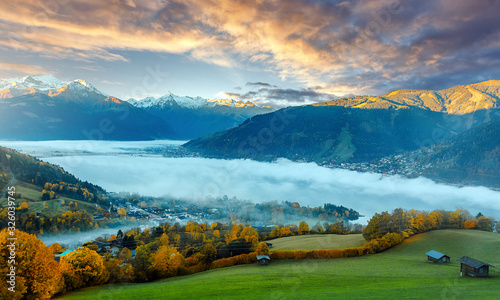 Wall mural - Amazing Autumn landscape on pink sunset. alpine farmland, pasture and high rocky mountains in background, Zell am See lake. Scenic View Of Zeller Lake and Tyrol Alps, Austria, Europe. Cretive image.