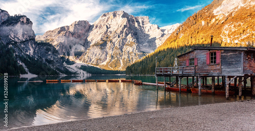 Wall mural - Sunny morning at Famouse Mountain Lake in dolomites Alps. Wonderful Braies Lake during sunrise. Amazing Summer Mountain Landscape. Lago di Braies in Spring, Awesome nature Scenery. Pragser wildsee
