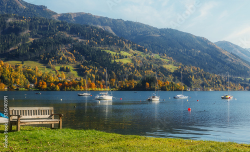 Wall mural - Fantastic views of the turquoise lake Zeller, under sunlight. Panoramic view on mountain lake with yachts, in front of mountain range. Awesome nature background. Landscape in Alps in sunny day.