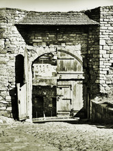 Medieval Castle In The City Of Kamyanets-Podilsky, Ukraine .  It Is A Formidable, Strong Fortress, Whose Walls Are Cut Out Of Solid. Black And White Photo. Sepia Photo. With A Special Artistic Effect.