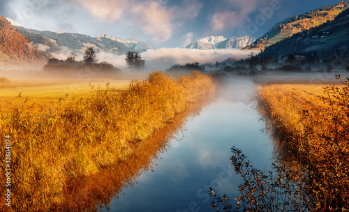 Wall mural - Wonderful picturesque Scene. Awesome Autumn landscape with colorful sky, reflected on the calm river. Amazing nature counryside. Impressive Misty Morning. Fantastic alpine scenery