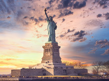 Famous Statue Of  Liberty And Dramatic Sky At Sunset With Orange Colors